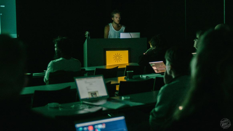 En person står längst fram i föreläsningssal och flera personer lyssnar med datorer framför sig.